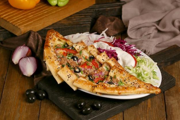 Türkische pide mit oliven und tomaten auf einem holzbrett