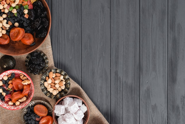 Türkische ramadanbonbons und -trockenfrüchte auf schwarzem holztisch