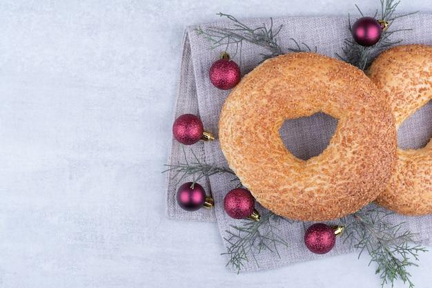 Türkische simits mit weihnachtskugeln auf tischdecke.