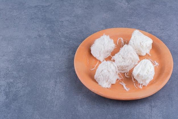 Türkische süße von zucker halvah pishmanie in einem teller auf einem stein.