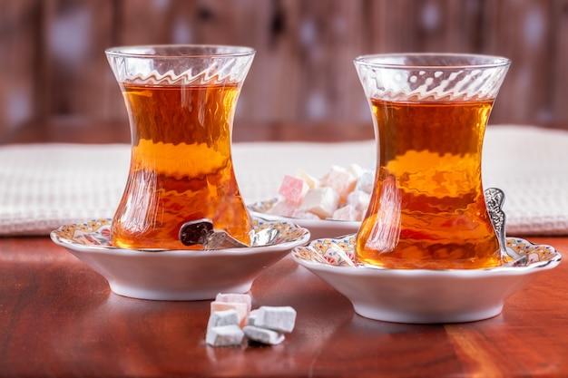 Türkische süßigkeiten und traditioneller türkischer tee in gläsern auf roter holzoberfläche
