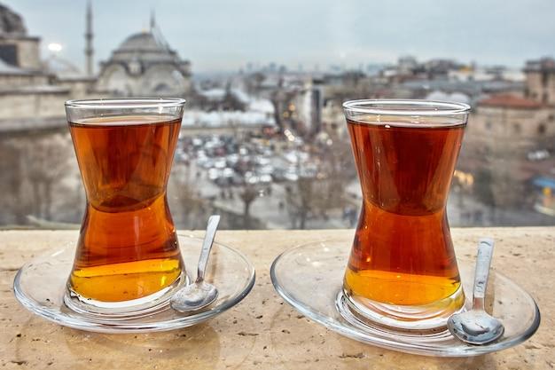 Türkische teegläser werden in untertassen mit löffeln gegen das stadtbild von istanbul gestellt.