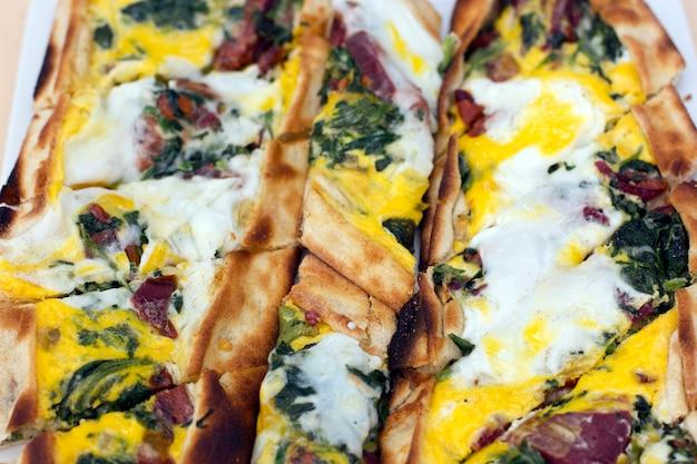 Türkische tortilla pita mit speck pastreurage, eiern und grünen kräutern.