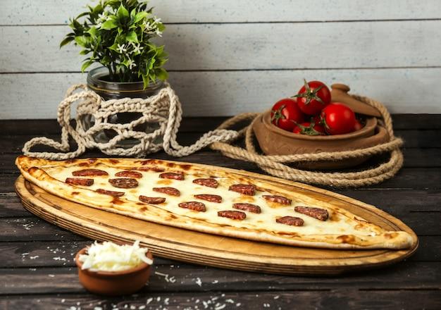 Türkische traditionelle pide mit käse und wurst auf einem holzbrett