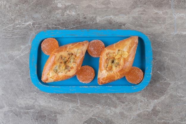 Türkische türkische pides und geleebonbons auf und neben einer kleinen platte auf marmoroberfläche