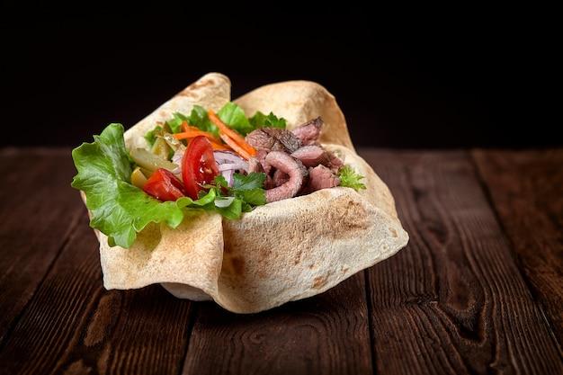 Türkische und arabische traditionelle mischungskebabplatte. kebabrindfleisch auf lavashbrot mit soße und gemüse.