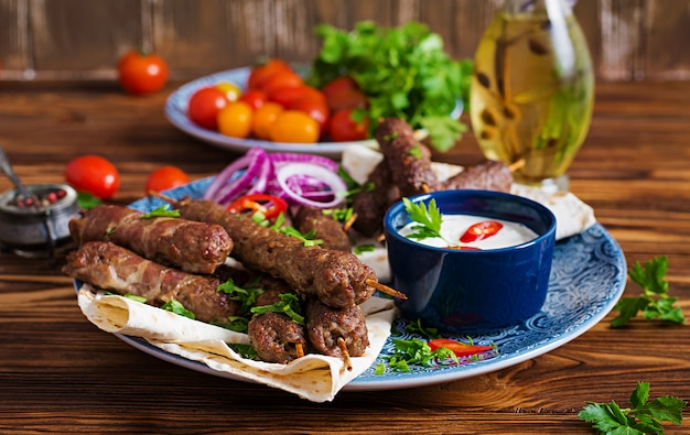 Türkische und arabische traditionelle ramadan-mischungskebabplatte. kebab adana, huhn, lamm und rindfleisch auf lavashbrot mit soße. ansicht von oben