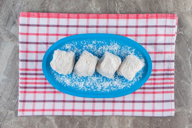 Türkische zuckerwatte in einer holzplatte auf geschirrtuch auf blau.