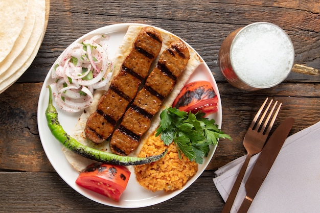 Türkischer adana kebap mit reispilaf und gemüse serviert auf einem teller