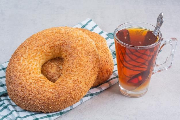 Türkischer bagel und eine tasse tee auf einem geschirrtuch auf dem marmor.
