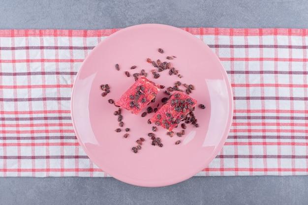 Türkischer genuss rahat lokum mit pistazien und trockenen rosinen auf rosa teller. draufsicht.