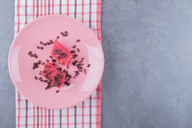 Türkischer genuss rahat lokum mit pistazien und trockenen rosinen auf rosa teller