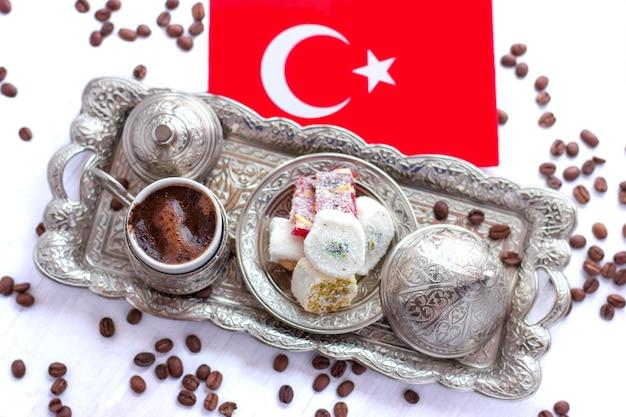 Türkischer kaffee auf einem traditionellen silbertablett mit türkischen süßigkeiten und der roten flagge der türkei
