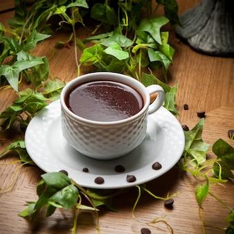 Türkischer kaffee der seitenansicht mit kaffeebohnen und traubenzweig in der tasse auf holztisch