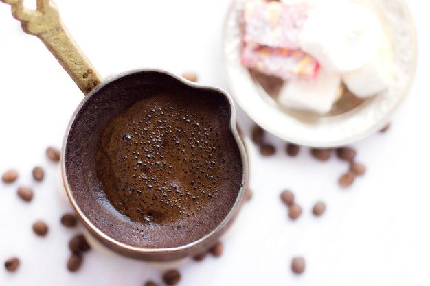 Türkischer kaffee im traditionellen jezve. türkische süßigkeiten