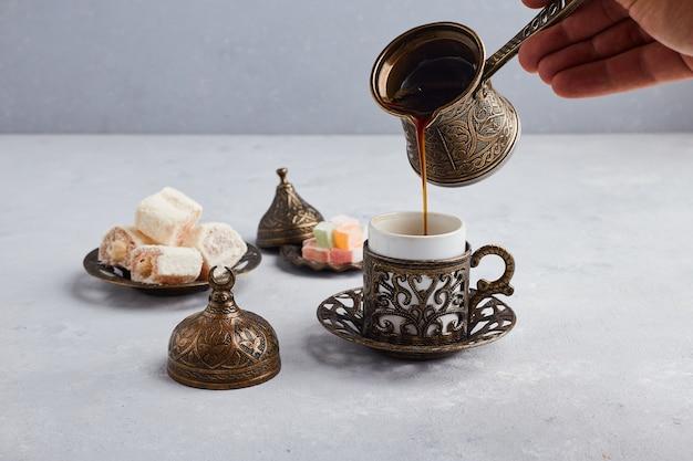 Türkischer kaffee in der metallischen kanne und tasse.