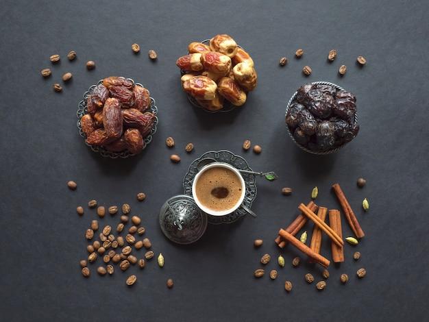 Türkischer kaffee mit daten und kardamom auf der schwarzen tabelle.