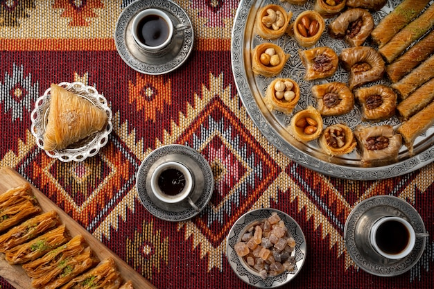 Türkischer kaffee und süßigkeiten serviert auf bunt gemustertem teppich