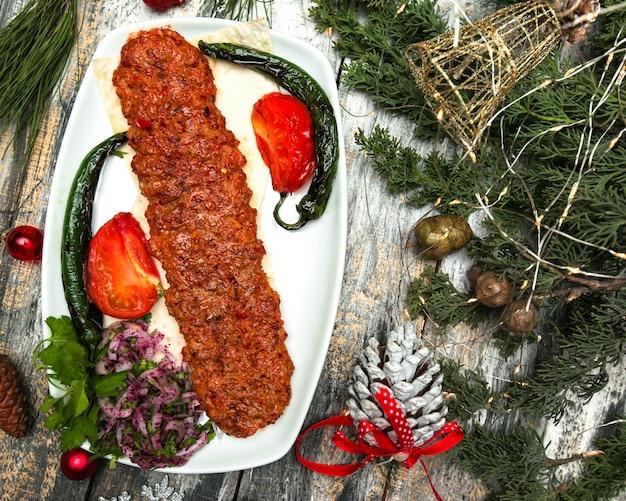 Türkischer kebab mit paprika-tomatenfleisch und gewürzen, serviert mit gegrilltem pfeffer und tomaten