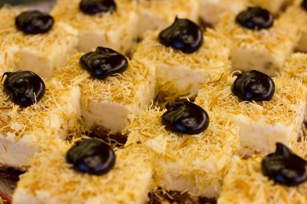 Türkischer nachtisch mit schwarzer schokolade und weißer sahne. geschnittener kuchen.