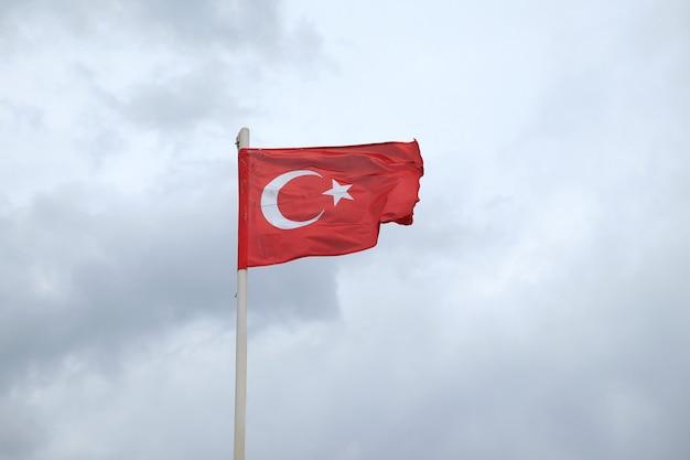 Türkischer roter flaggenwitz mit stern und halbmond, die auf fahnenmast am bewölkten tag gegen starke graue regenwolken winken
