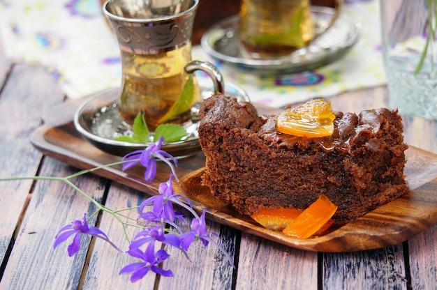 Türkischer schokoladenkuchen mit kandierten zitronenschalen und tassen minztee