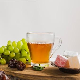 Türkischer tee im becher mit süßigkeiten und früchten