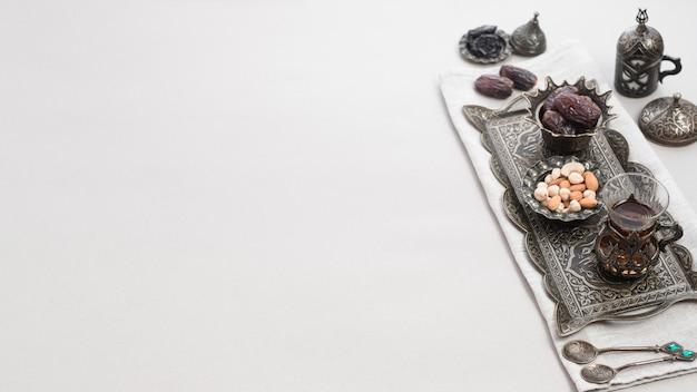Türkischer tee im glas und datum trägt zum nachtisch auf dem orientalischen behälter früchte, der über weißem hintergrund lokalisiert wird