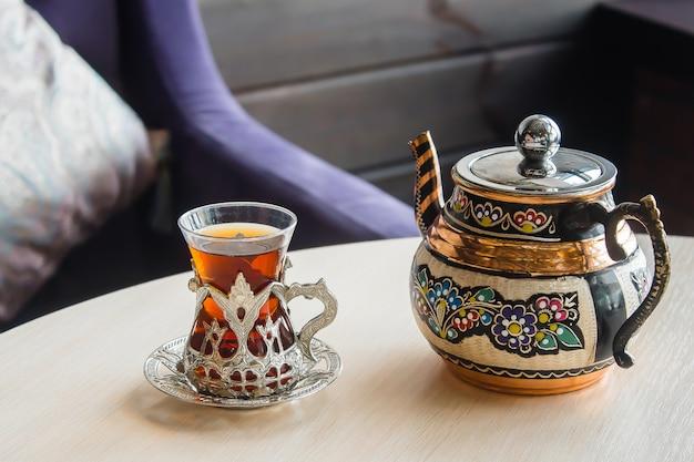 Türkischer tee im traditionellen glas auf dunkler tabelle