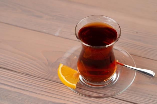 Türkischer tee in der glasschale mit dem stück zitrone auf holztisch