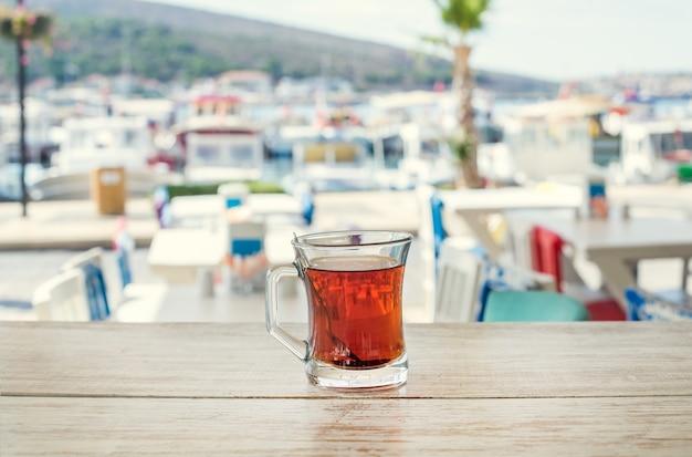 Türkischer tee in der traditionellen glasschale auf holztisch mit der hintergrundansicht des seehafens