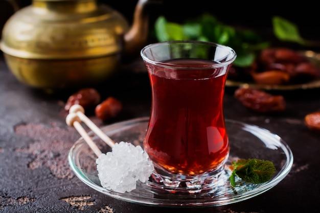 Türkischer tee in traditioneller glasschale mit karamellisiertem zucker und minze im dunkeln