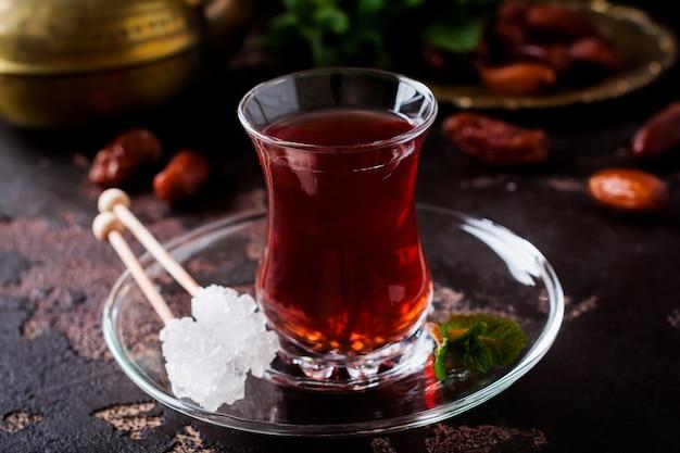 Türkischer tee in traditioneller glastasse mit karamellisiertem zucker und minze auf dunklem hintergrund