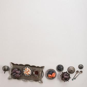 Türkischer tee; termine; nüsse auf orientalischem metallbehälter und schüssel lokalisiert über weißem hintergrund