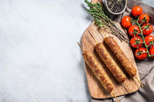 Türkischer und arabischer traditioneller kebab auf schneidebrett, rinderhackfleisch, lammfleisch