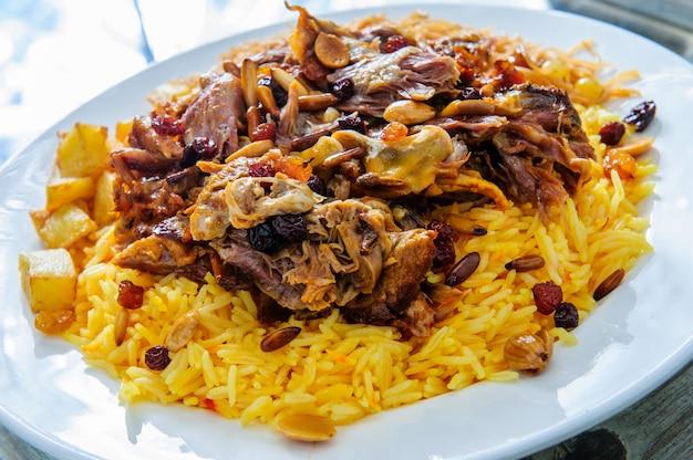 Türkischer und arabischer traditioneller leber-doner-kebab, der witt salat, joghurt, salat, fladenbrot, zwiebel, tomaten- und reispilav in weißer platte auf garniturrestauranthintergrund dient