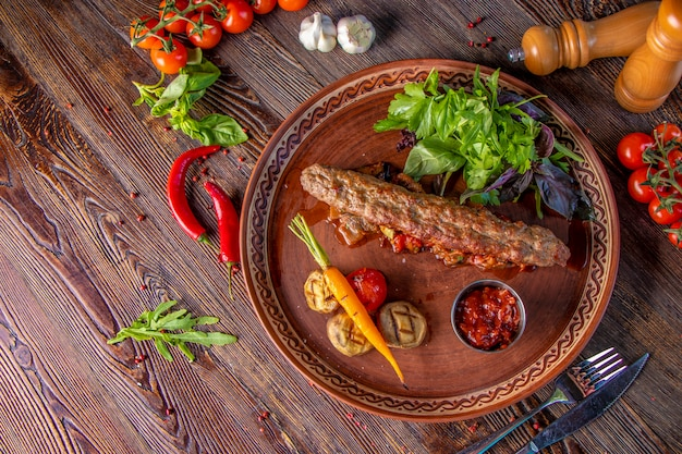 Türkischer und arabischer traditioneller ramadan mischen kebabplatte, kebablamm und rindfleisch mit gebackenem gemüse, pilzen und tomatensauce. draufsicht, nahaufnahme