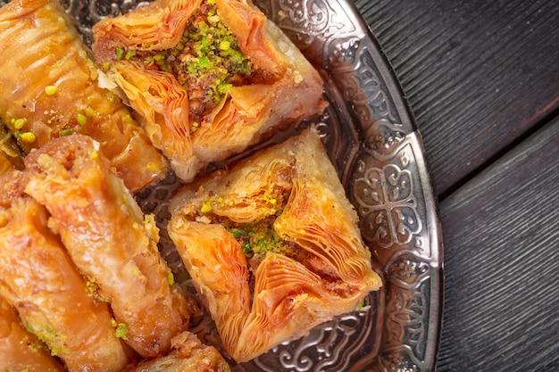 Türkisches arabisches nachtischbaklava mit honig und nüssen auf einer silbernen platte