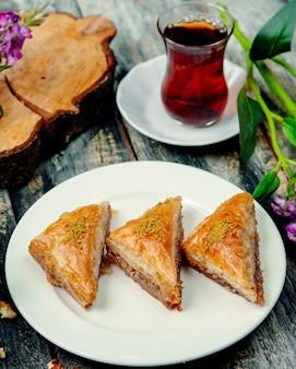 Türkisches baklava mit nüssen und einer tasse heißem tee