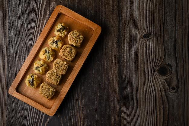 Türkisches baklava süßes gebäck auf holztablett isolierter holzhintergrund