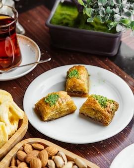Türkisches baklava von der seite mit nüssen und einem glas tee