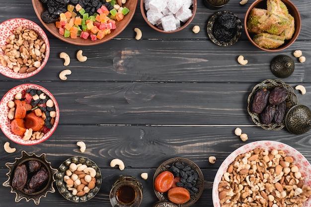 Türkisches dessert baklava; lukum mit trockenfrüchten und nüssen auf holztisch mit kopienraum in der mitte