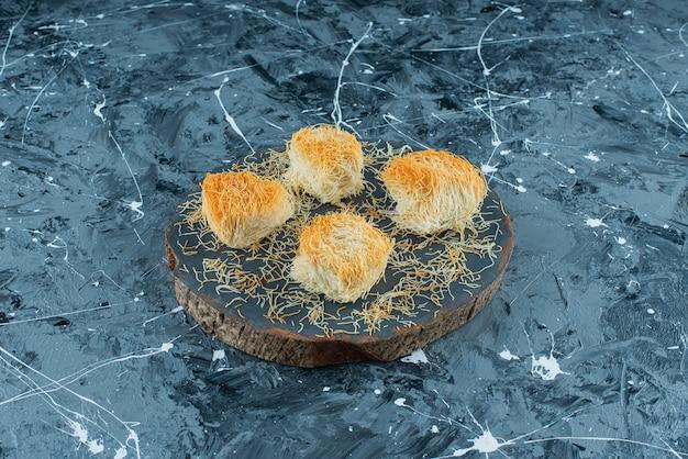 Türkisches dessert kadayif auf einem brett auf dem blauen tisch.