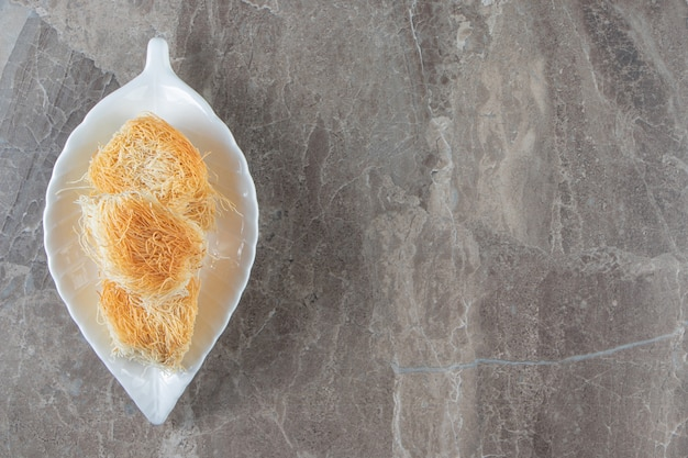 Türkisches dessert kadayif auf einem teller auf blau.