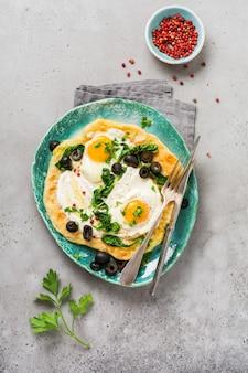 Türkisches eierfladenbrot mit joghurt, käse, oliven, spinat und rotem pfeffer auf keramischer vintage-platte auf grauem alten hintergrund. ansicht von oben.