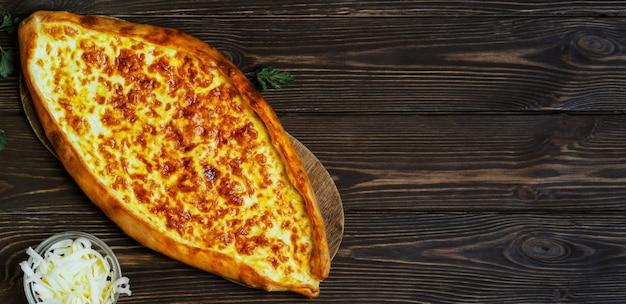 Türkisches fladenbrot (pide) mit käse. kasarli pide auf dem dunklen holztisch. flach mit kopierraum liegen. traditionelle türkische pizza