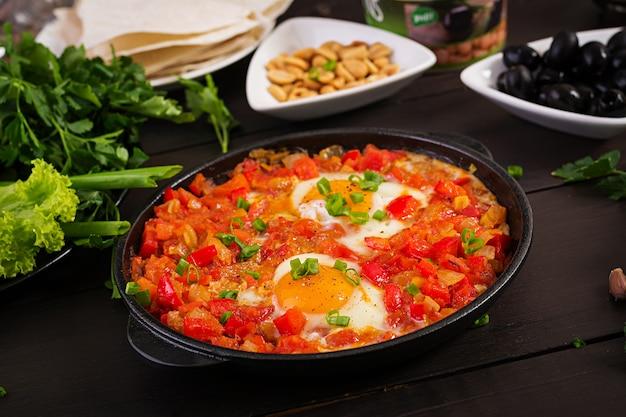 Türkisches frühstück - shakshuka, oliven, käse und obst.