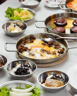 Türkisches frühstücks-setup mit ei und fleischgericht in stahlpfanne gekocht