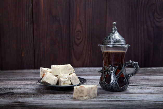 Türkisches glas mit tee und halva auf einem metallplattenständer auf einem hölzernen hintergrund.