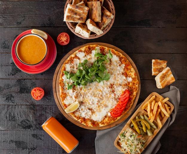 Türkisches lahmajun mit käse, serviert mit zitrone, petersilie mit tomatensuppe
